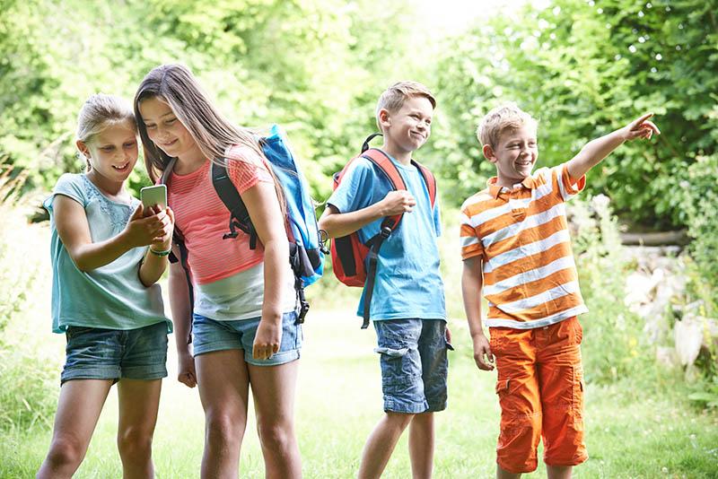 Groep kinderen geocachen in het bos